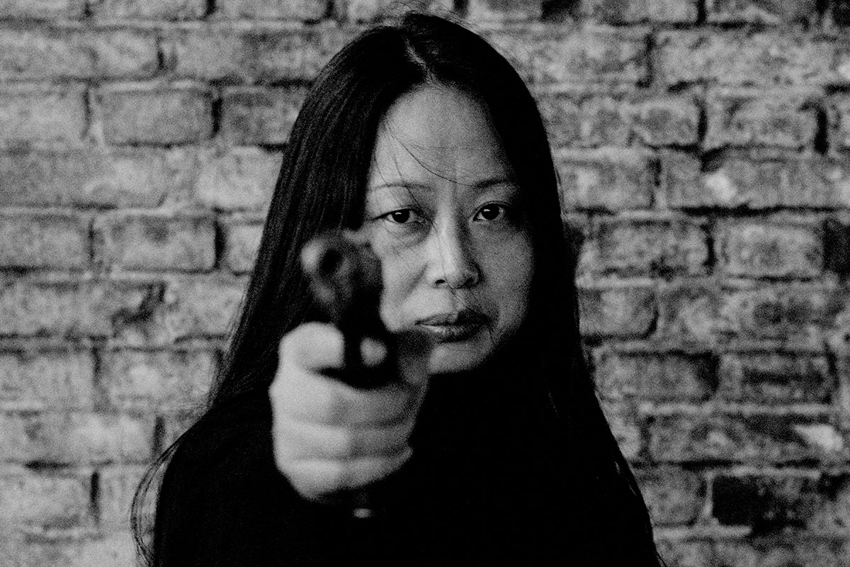A black and white photograph of a woman (the artist) holding a gun, pointing it in the direction of the viewer and making eye contact with the viewer.